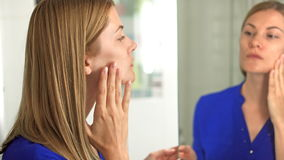 深蓝女衬衫的美丽的可爱的少妇检查她的在镜子的面孔在卫生间里 股票录像