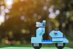 深蓝摩托车塑料砖戏弄在绿色塑料板材的立场有模糊的树背景 免版税库存图片