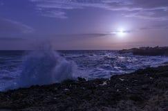 深蓝日落 在风大浪急的海面期间的海岸线 图库摄影
