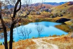 深蓝湖和秋天小山 库存图片