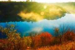 深蓝湖和金黄阳光和秋天树 免版税库存图片
