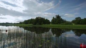 深蓝湖水美丽的景色与荷花的和在日落的绿色薹 股票录像