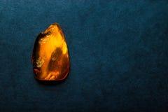 深蓝背景表面上的琥珀色的石头与自由空间 库存照片