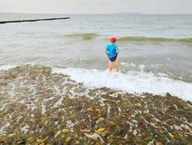 深蓝色运动的衣裳的男孩在冷的泡沫似的海停留 在波浪的金发孩子 免版税库存图片