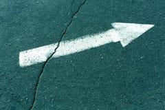 深蓝被定调子的沥青表面上的白色箭头 免版税库存照片
