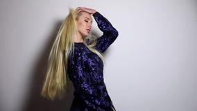 深蓝长的礼服姿势的美丽的性感的白肤金发的妇女反对演播室背景 慢动作英尺长度 股票视频
