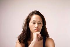 深刻的想法的亚裔中国夫人有桃红色背景 免版税库存照片