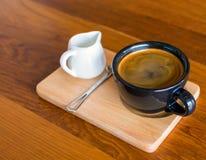 深黑色蓝色咖啡杯用americano咖啡、匙子和一个牛奶罐在一个木立场 免版税图库摄影