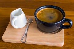 深黑色蓝色咖啡杯用americano咖啡、匙子和一个牛奶罐在一个木立场 库存图片