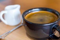 深黑色蓝色咖啡杯用americano咖啡、匙子和一个牛奶罐在一个木立场 免版税库存照片