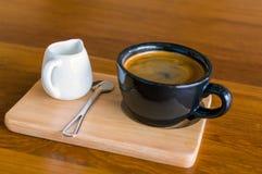 深黑色蓝色咖啡杯用americano咖啡、匙子和一个牛奶罐在一个木立场 免版税库存图片