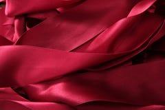 混乱杂乱红色丝带缎纹理 免版税库存照片
