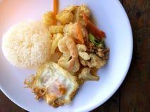 混乱油炸物菜用豆腐和虾在白色盘用米和煎蛋在木背景 泰国食物的样式 免版税库存图片