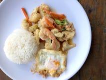 混乱油炸物菜用豆腐和虾在白色盘用米和煎蛋在木背景 泰国食物的样式 免版税图库摄影
