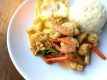 混乱油炸物菜用豆腐和虾在白色盘用米和煎蛋在木背景 泰国食物的样式 库存图片