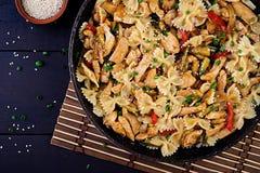 混乱油炸物鸡、面团farfalle、夏南瓜、甜椒和大葱 免版税库存照片