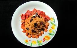 混乱油煎的意粉用干辣椒和香肠,火腿 免版税图库摄影