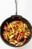 混乱油煎的牛排用在被隔绝的背景的胡椒 免版税库存图片