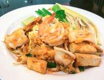 混乱油煎的米线用虾和乌贼在白色板材 库存图片