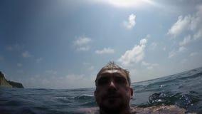 混乱照相机移动POV在白种人人前面的水到海里,然后浮游物下 股票视频