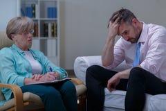 混乱的商人谈话与精神病医生 免版税库存图片