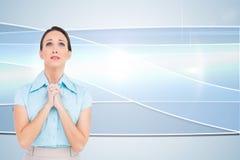 混乱的年轻女实业家祈祷 库存图片