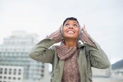 混乱的年轻模型在冬天给堵塞她的耳朵穿衣 免版税图库摄影
