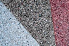 混凝土墙和多彩多姿的石渣的背景与三部分-白色、灰色和红色纹理  水平的框架 免版税图库摄影