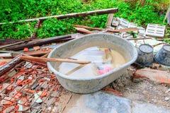 混凝土搅拌机塑料空在安排在垃圾木材堆的水在建筑房子更新站点和日出光 免版税库存照片