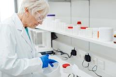 混合一些药物或医学的药剂师妇女在实验室 库存照片