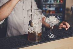 混合世界性鸡尾酒的年轻侍酒者 免版税库存照片