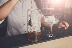 混合世界性鸡尾酒的年轻侍酒者 图库摄影