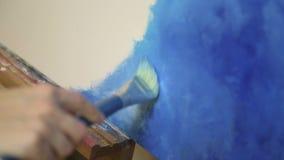 混合丙烯酸酯的颜色的艺术家手与在调色板的刷子 股票录像
