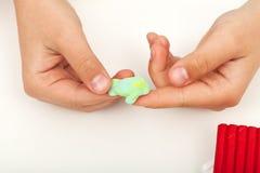 混合两个颜色的黏土的儿童手 免版税库存照片
