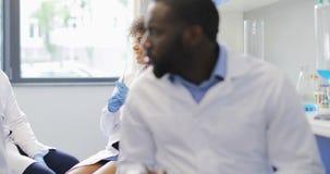 混合分析在试管的种族团体科学家化学制品,当工作在研究员实验室时 股票录像
