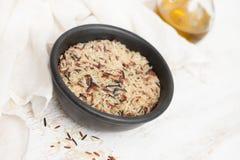 混合在小黑碗的米在白色背景 免版税库存照片