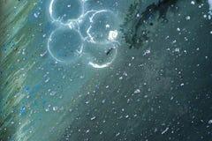 混合在水关闭下的五颜六色的液体  免版税库存照片