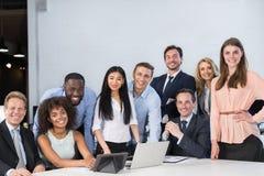 混合坐在表愉快的微笑的会议通信讨论、商人和妇女工作的种族买卖人 库存照片