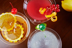 混合明亮的可口鸡尾酒顶视图与桔子和一棵樱桃片断的装饰的在桌上在餐馆有bac的 免版税库存图片