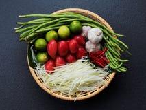 混合泰国绿色番木瓜沙拉,番木瓜,蕃茄,石灰,大蒜,辣椒,在棕色篮子的豆成份在黑暗的背景 免版税图库摄影