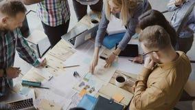 混合的族种人顶视图站立在桌附近的 一起研究起始的项目的年轻企业队 股票录像