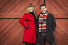 混合的族种在冬天衣物的夫妇画象反对毂仓大门 库存照片