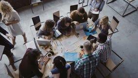 混合的族种坐在桌上的企业队顶视图在顶楼办公室和工作 妇女经理带来本文 免版税库存照片