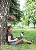 混合的族种大学生坐草工作 免版税库存图片