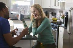 混合的族种夫妇谈话在厨房里,妇女笑 免版税图库摄影