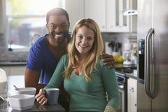 混合的族种夫妇画象在厨房,倾斜的人里下来 免版税图库摄影