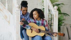 混合的族种少妇坐教她的少年姐妹的台阶在家弹声学吉他 免版税图库摄影