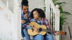 混合的族种少妇坐教她的少年姐妹的台阶在家弹声学吉他 免版税库存照片