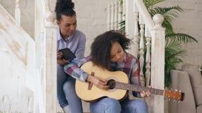 混合的族种少妇坐教她的少年姐妹的台阶在家弹声学吉他 影视素材