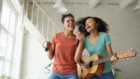 混合的族种年轻滑稽的女孩跳舞唱歌与hairdryer和弹在床上的声学吉他 有的乐趣姐妹 免版税库存照片